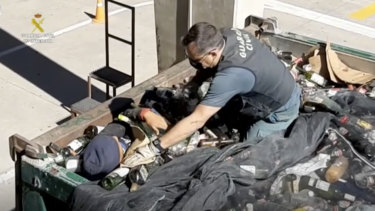 An officer helps a man out from under glass bottles in a container in Melilla, Spain.