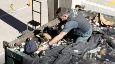 Un funcionario de The Guardian ayuda a sacar botellas de vidrio de debajo de un contenedor en Melilla, España.