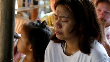 The mother of the slain girl Myka Ulpina cries during mass at her wake.