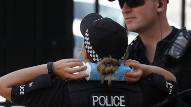 A police officer cools down with a drink carton held on her neck as temperatures pass 38 degrees in London on Thursday.