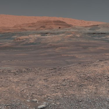 Welcome to Mars, where Mount Sharp rises in the distance. In the middle ground are clay-bearing rocks that scientists hope will help ascertain the role of water on the planet.