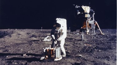 Buzz Aldrin deploys an experiment on the surface of the moon.