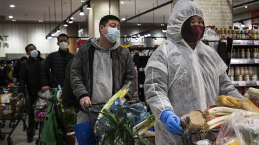 Chinese residents wear protective gear as they line up in a supermarket in Wuhan.