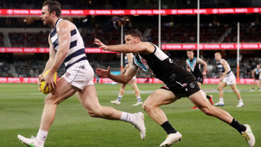 A lunging Travis Boak in pursuit of Cat Patrick Dangerfield in the qualifying final between Port Adelaide and Geelong.