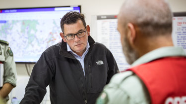Premier Daniel Andrews is briefed by emergency services personnel.