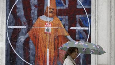 A pedestrian passes street art depicting Julian Assange near Westminster Magistrates' Court in London where he appeared.