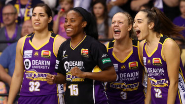 Lindsay Allen (second left) cheers her team on from the sideline.