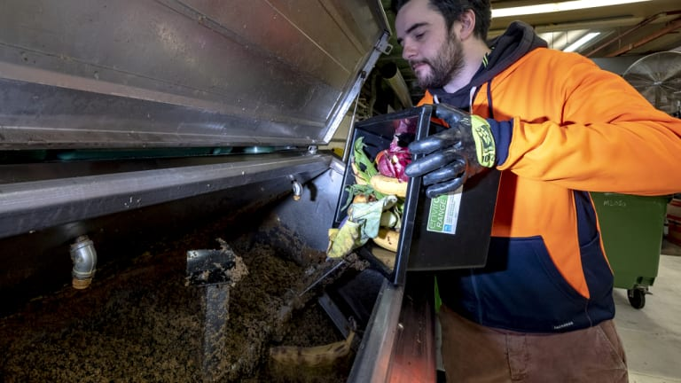 Niall Haran tips some restaurant waste into the ORCA aerobic food digester.