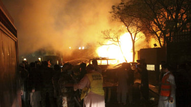 A police officer and rescue workers arrive at the site of bomb blast in Quetta, Pakistan.