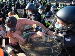 Police clash with protestors at the Shrine on Wednesday. The occupation of the shirtless gentleman is unknown, although we note he is wearing Tradie underwear. Sadly, his refreshing can of Wild Boar bourbon and cola appears to have been collateral damage in the fracas.