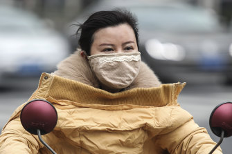 A woman wears a mask in Wuhan, where the virus is believed to have originated.