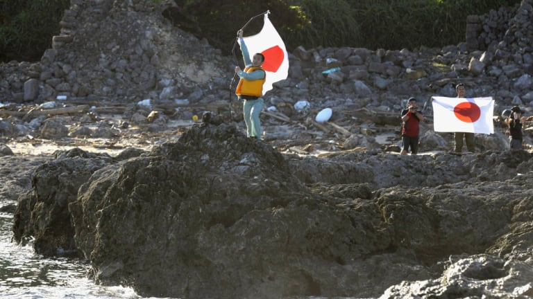 Japanese activists hold the national flags on Uotsuri island, one of the islands of Senkaku in Japanese and Diaoyu in Chinese, in East China Sea in 2012.