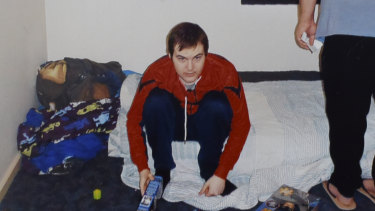 Reece sits on a mattress on the floor in his bedroom last year.