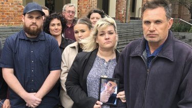 Pamela and Chris Fink, far right, were surrounded by family and supporters during the Supreme Court hearing where they sought to get an inquest into their son's suicide.