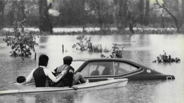 Two people in a canoe inspect a flooded car at Lansvale, August 6, 1986.