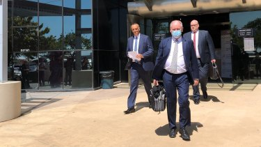 John Osborne from Ardent Leisure (left) and Bruce Hodgkinson, QC, wearing a mask, leave Southport Magistrates Court.