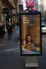 A Telstra telephone booth in Melbourne's Collins Street with an advertising display sign tacked on the side.