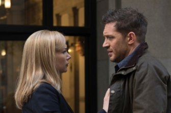 """This image released by Sony Pictures shows Michelle Williams, left, and Tom Hardy in a scene from """"Venom."""" (Frank Masi/Sony Pictures via AP)"""