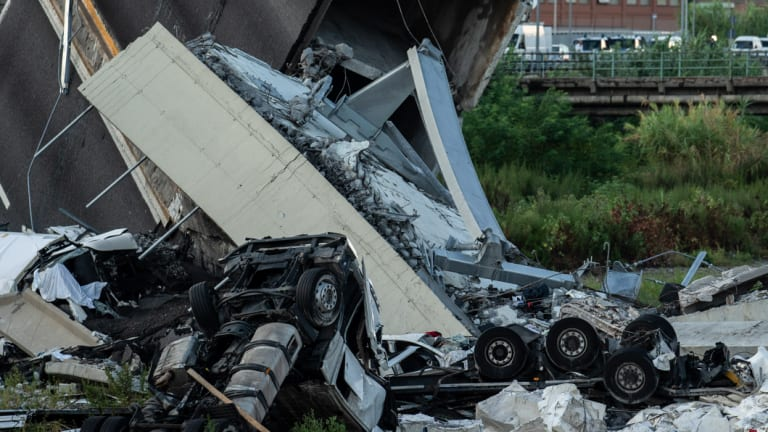 Chassis of vehicles and rubble from the Morandi Bridge sit on the ground after the collapse.
