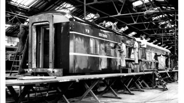Painters at Newport Workshops in 1973 put finishing touches on the Victorian Railways new luxury twinette carriage which will be operated with the Spirit of Progress train.