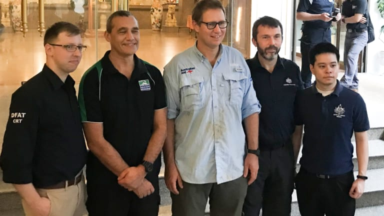 Craig Challen (second from left), Dr Richard Harris (centre) with DFAT staff at his hotel on Wednesday.