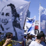 Musicians play as tens of thousands march against the economic policies of Argentina's government, in Buenos Aires, with some holding banners picturing Evita, left.