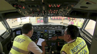 Investigators inspect the cockpit of a Boeing 737 MAX 8 aircraft in hangar in Indonesia.