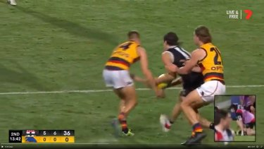 Adelaide's David Mackay and St Kilda's Hunter Clark simultaneously lunge for the ball. Clark ended up with a broken jaw.