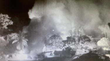 CCTV footage shows the smoke from burning homes in Aurukun during the unrest on New Year's Day.