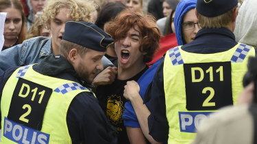 "Police push back people protesting a far-right ""Alternative For Sweden"" campaign meeting in Kungstradgarden park in Stockholm on Friday."