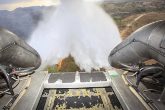 In this photo released by Brazil's Ministry of Defence, a C-130 Hercules aircraft dumps water to fight fires raging in the Amazon.