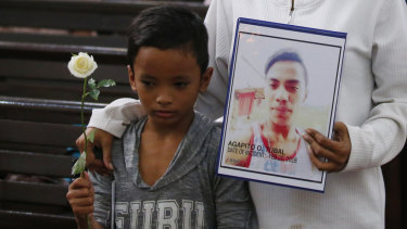 A boy stands next to his mother, who holds a portrait of his brother, an alleged victim of President Rodrigo Duterte's 'war on drugs', during a religious service in Manila last month.