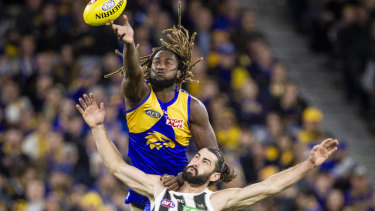 Eagle Nic Naitanui soars over Brodie Grundy at Optus Stadium.