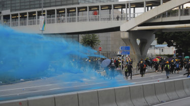 A police vehicle sprays blue-coloured water at anti-government protesters.