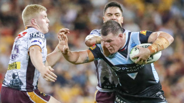 One who can hold his head high: Cronulla captain Paul Gallen drives forward against the Broncos.