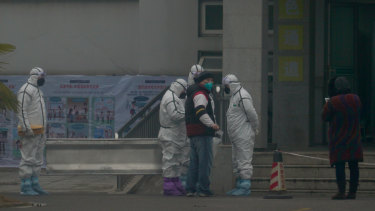 Staff in biohazard suits outside a hospital in Wuhan.