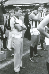 Collingwood coach Tom Hafey stands with his players after their loss.