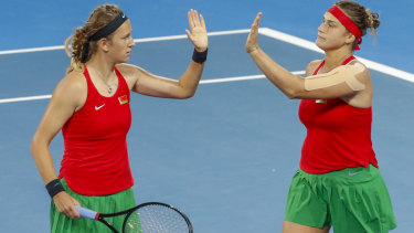 Aryna Sabalenka (right) and Victoria Azarenka (left) of Belarus celebrate winning the second set in the decisive fifth rubber.