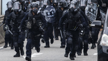 Riot police charge towards protesters on Lung Wo Road during a protest against a proposed extradition law in Hong Kong.
