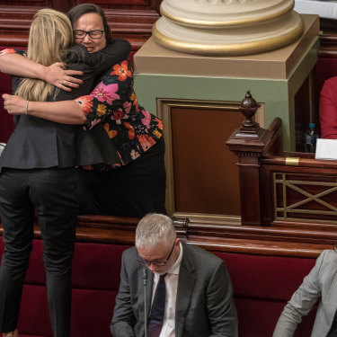 After a marathon 29 hours sitting to pass the Voluntary Assisted Dying Bill, Fiona Patten of the Reason Party stands on the seats to hug Labor's Harriet Shing after the vote passes.