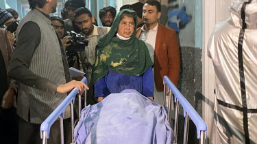 Afghans carry the body of a woman, one of three media workers killed by gunmen in Jalalabad, east of Kabul, Afghanistan.