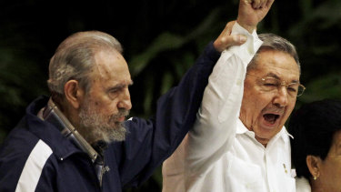 Fidel Castro, left, raises the hand of his brother President Raul Castro as they sing the international socialism anthem in 2011.