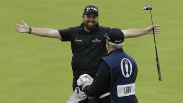Ireland's Shane Lowry celebrates on the 18th green with his caddie Bo Martin after winning the British Open at Royal Portrush in Northern Ireland on Sunday.
