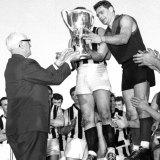 Melbourne's Ron Barassi receives the 1964 premiership cup.