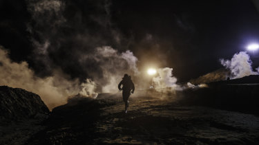 Migrants run as tear gas from US Border Protection officers is shot to the Mexican side of the border fence.