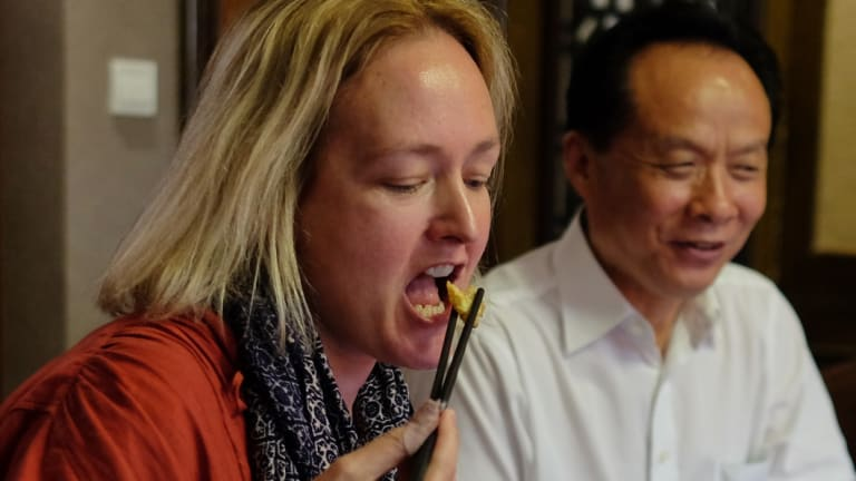 Fairfax China Correspondent Kirsty Needham tasting a fried American cockroach at a local restaurant.