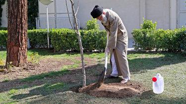 Supreme Leader Ayatollah Ali Khamenei, wearing gloves, participates in a tree planting ceremony in Tehran, Iran.