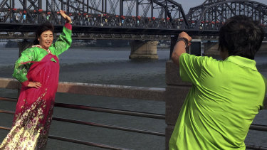 Chinese tourists in North Korean costumes pose for souvenir photos near the Friendship Bridge connecting China and North Korea.
