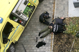 Police detain a main next to a damaged ambulance in Oslo.