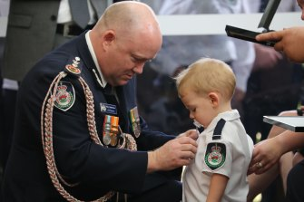 RFS Commissioner Shane Fitzsimmons pins the service medal of Geoffrey Keaton onto his son, Harvey.